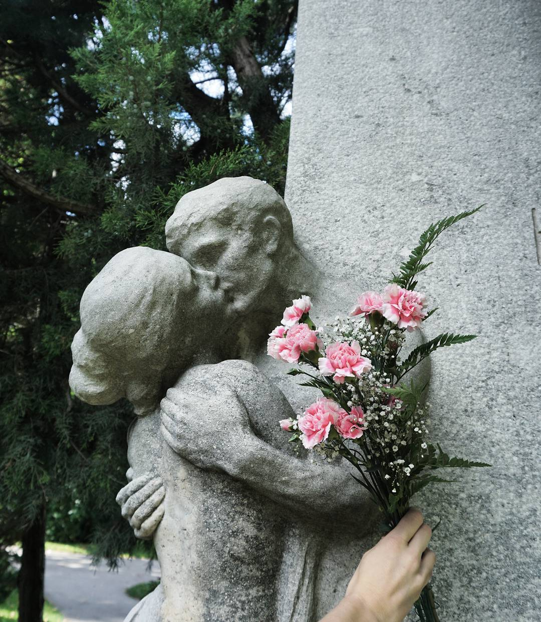 statue on graveyard with flowers