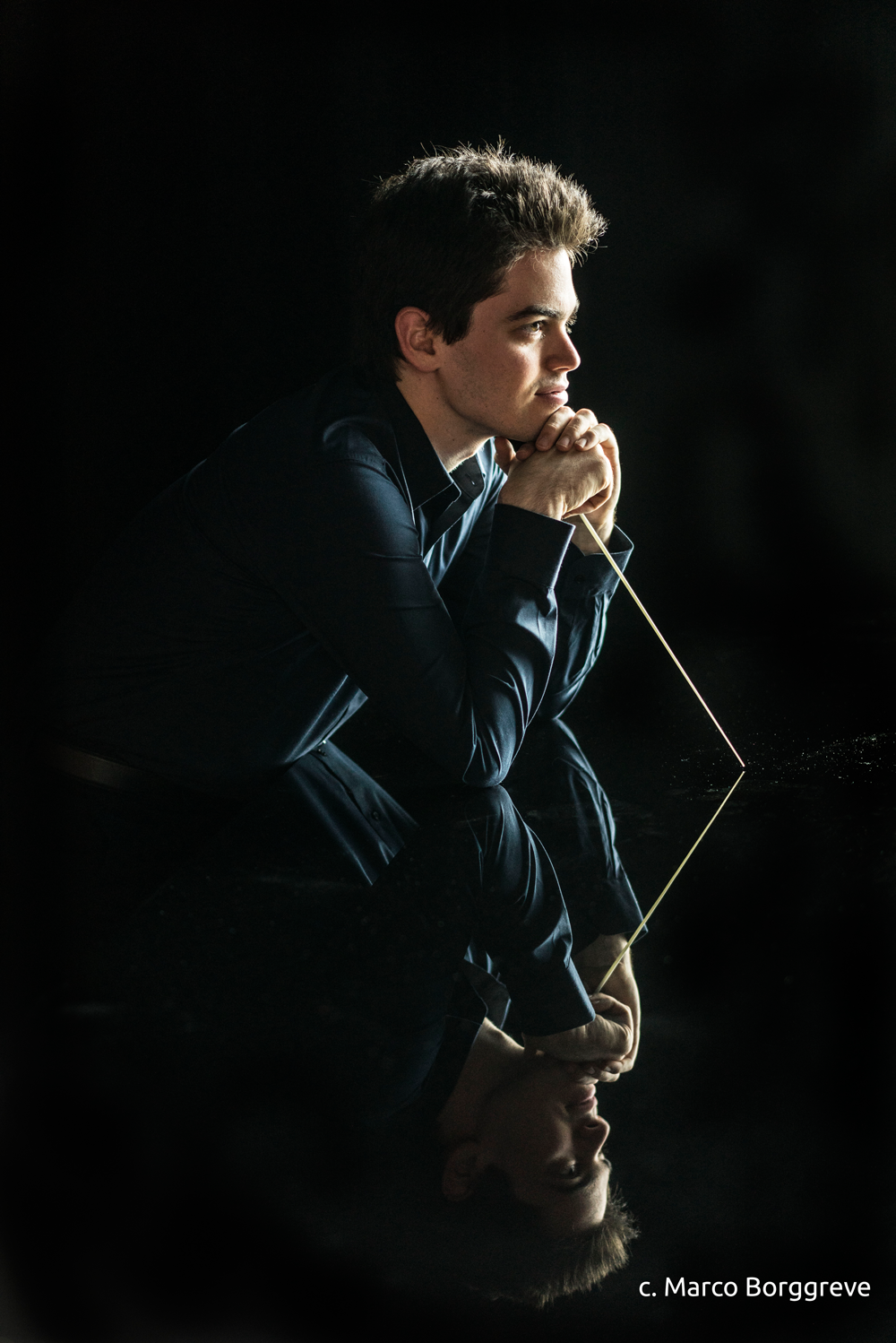 conductor looking pesive into the distance with black background and reflection